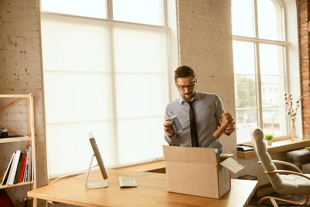 Um jovem empresário se mudando no escritório