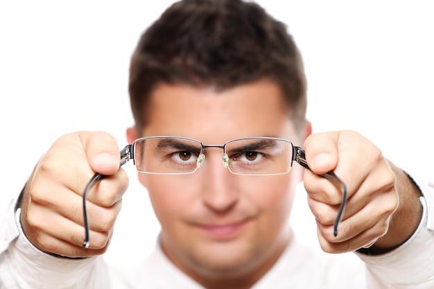 Um jovem empresário segurando óculos, foco nos olhos e óculos