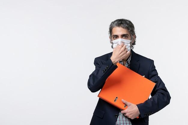 Um jovem empresário sério de terno segurando sua máscara cirúrgica e segurando seus documentos na superfície branca