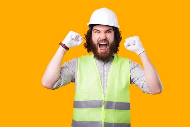 Um jovem engenheiro chateado está olhando para a câmera gritando com as duas mãos para cima perto de uma parede amarela