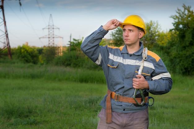 Um jovem engenheiro eletricista, usando um capacete protetor amarelo