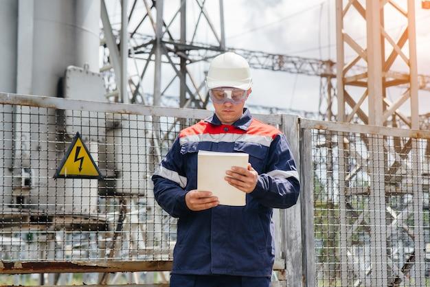 Um jovem engenheiro está de máscara em uma subestação elétrica.