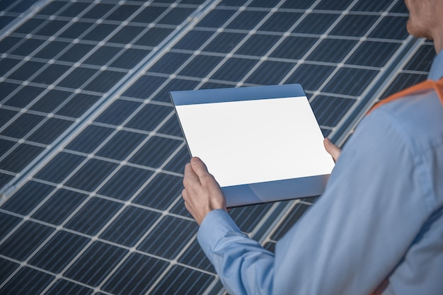 Um jovem engenheiro está verificando com tablet uma operação de sol e limpeza no campo de painéis solares fotovoltaicos em um pôr do sol. conceito: energia renovável, tecnologia, eletricidade, serviço, verde, futuro.