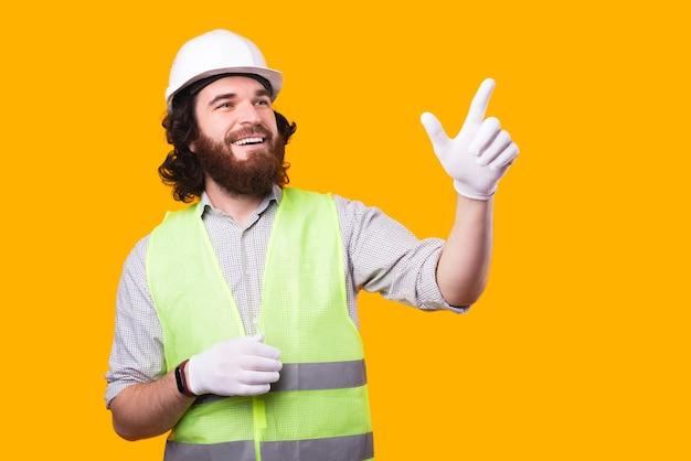Um jovem engenheiro feliz está desviando o olhar tentando tocar em algo em um espaço livre perto de uma parede amarela