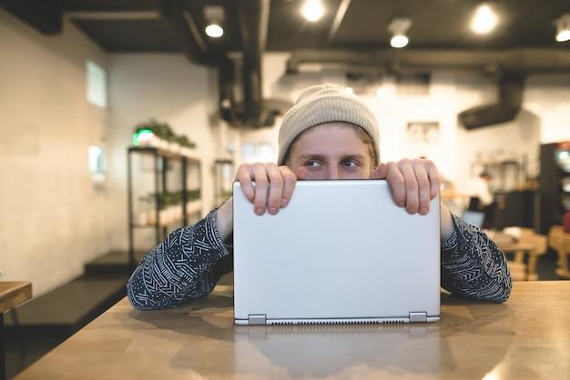 Um jovem engraçado, se escondendo atrás de um laptop. descolados alegres trabalham no computador em um café aconchegante. desvie o olhar.
