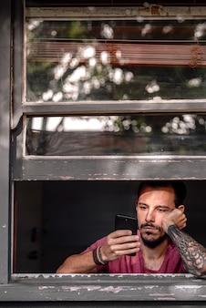 Um jovem entediado durante o bloqueio do covid 19 devido a uma overdose de smartphone.