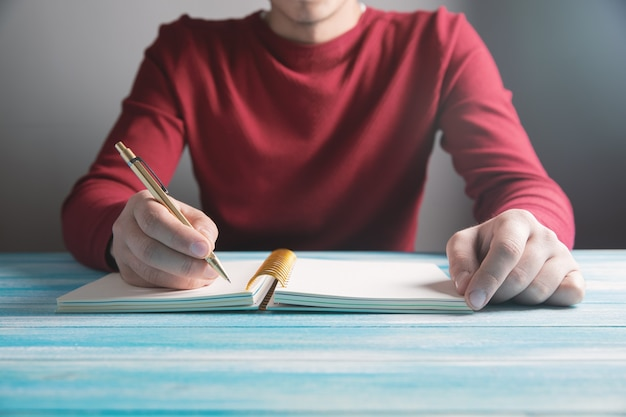 Um jovem escreve em um caderno