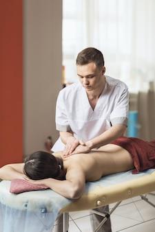 Um jovem especialista realiza uma massagem geral para seu cliente no consultório