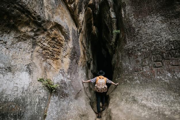 Um jovem espeleólogo amador entra em uma caverna na montanha com uma mochila