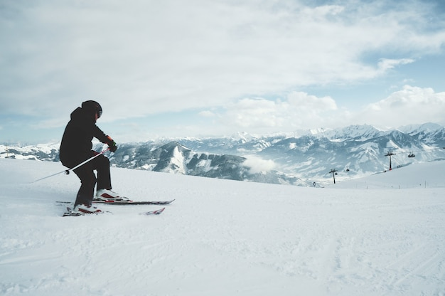 Um jovem esquiando nas montanhas cobertas de neve