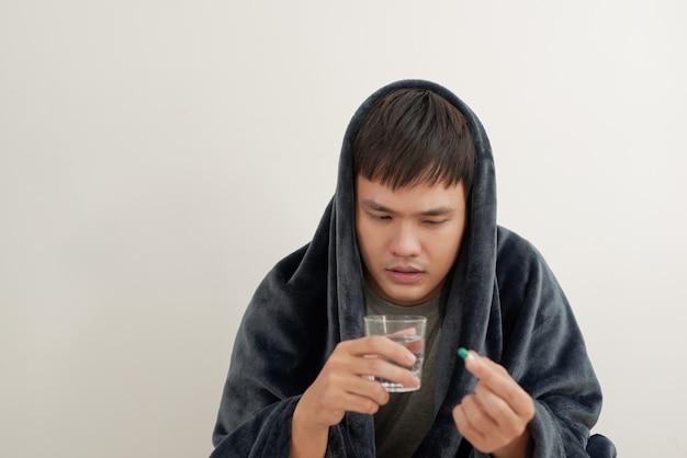 Um jovem está com gripe, deita-se em casa debaixo de um cobertor, toma um comprimido