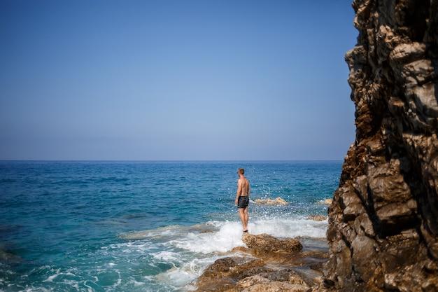 Um jovem está de pé nas rochas com vista para o mar mediterrâneo aberto. um cara em um dia quente de sol de verão olha para a brisa do mar