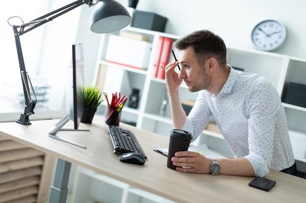 Um jovem está de pé perto de uma mesa no escritório, segurando um lápis e um copo de café