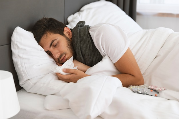 Um jovem está deitado na cama. ele está doente, tem alta temperatura corporal, coriza e tosse.