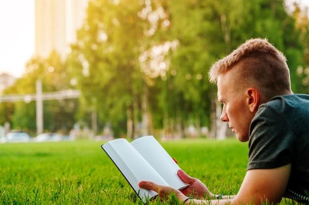 Um jovem está deitado no parque, na grama, olhando para um caderno de livro