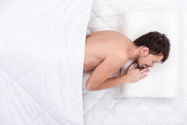 Um jovem está dormindo em um colchão branco.