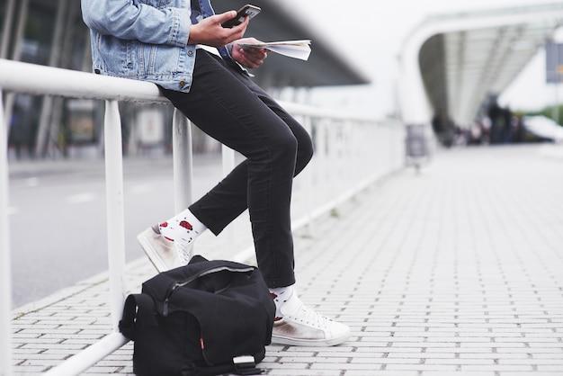 Um jovem está esperando por um passageiro no aeroporto.