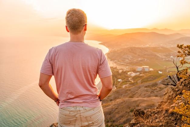 Um jovem está na beira de um penhasco ao pôr do sol com uma vista incrível das montanhas