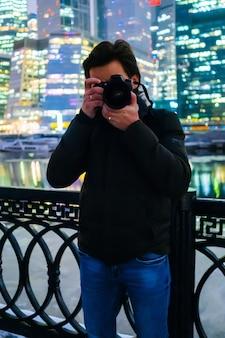Um jovem está parado no fundo da cidade de moscou e olha para a câmera