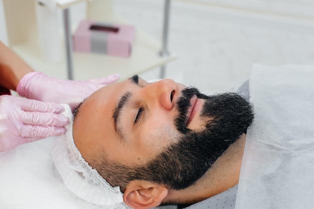 Um jovem está passando por um procedimento de peeling facial cosmético