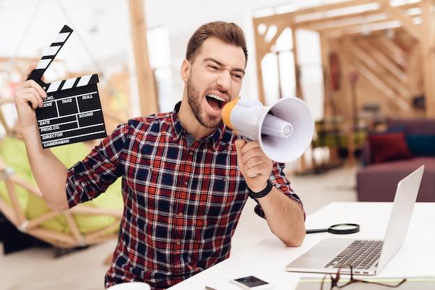 Um jovem está posando em uma câmera com um badalo de filme.