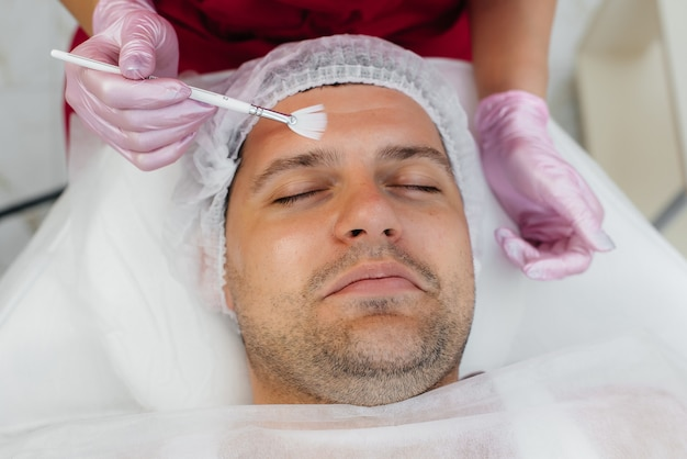 Um jovem está sendo submetido a um procedimento de peeling facial cosmético. cosmetologia e rejuvenescimento.