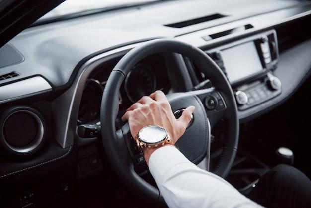 Um jovem está sentado em um carro recém-comprado, segurando as mãos em um leme.