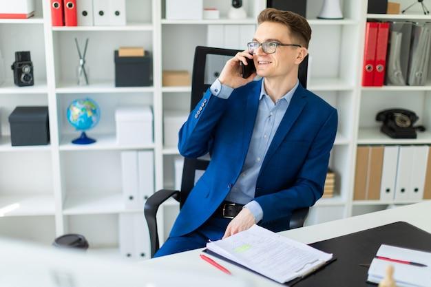 Um jovem está sentado em uma mesa no escritório e falando ao telefone.