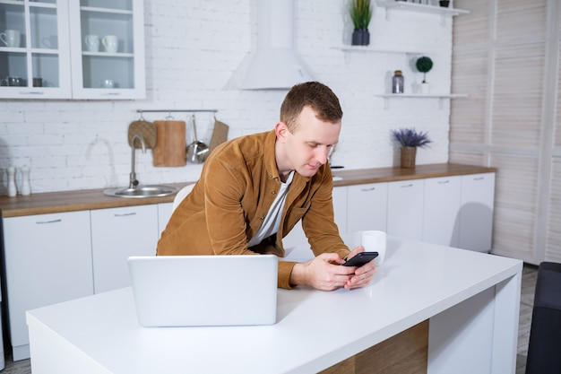Um jovem está sentado na cozinha com um laptop e falando ao telefone. trabalho remoto.
