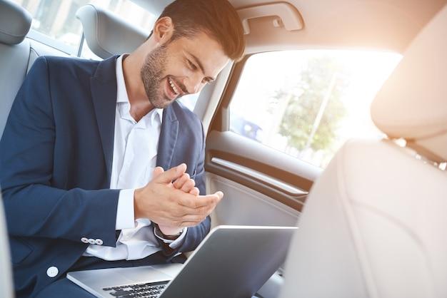 Um jovem está sentado no carro apreciando a transação bem-sucedida