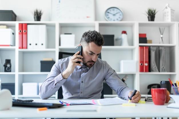 Um jovem está sentado no escritório, falando ao telefone e segurando um marcador na mão.