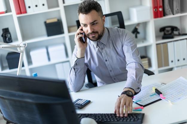 Um jovem está sentado no escritório, falando ao telefone e trabalhando no computador.
