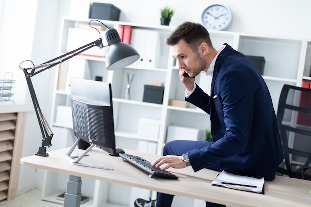 Um jovem está sentado no escritório na mesa, falando ao telefone e trabalhando com um computador