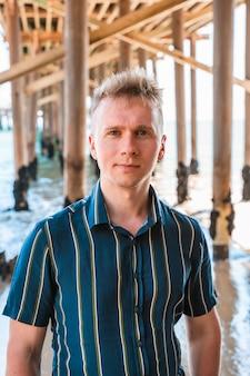 Um jovem está sob um píer na praia de malibu, na califórnia