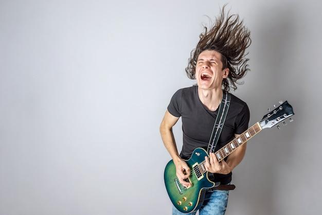 Um jovem está tocando uma guitarra elétrica cantando e balançando seus longos cabelos