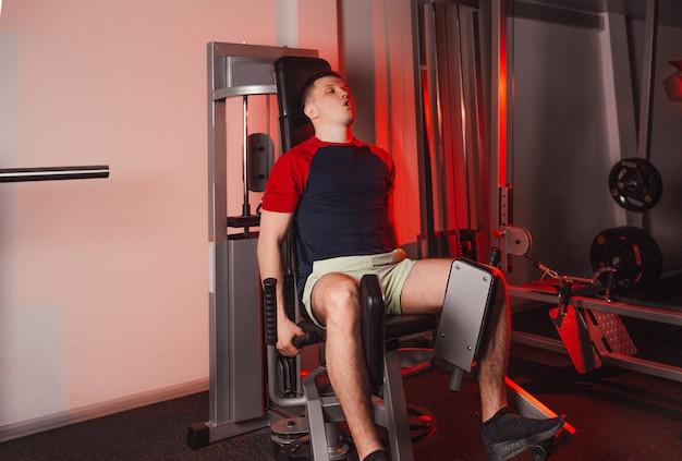 Um jovem está treinando suas pernas enquanto está sentado em um simulador na academia. treinamento de força