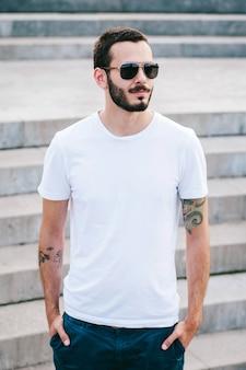 Um jovem estiloso com barba, usando uma camiseta branca e óculos