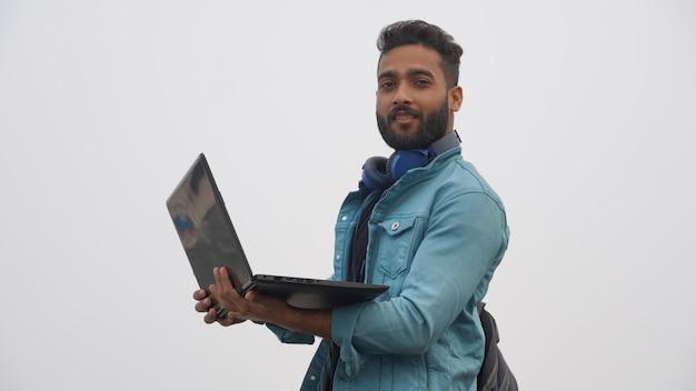 Um jovem estudante com laptop e fone de ouvido conceito de educação