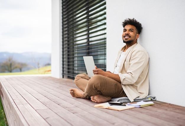 Um jovem estudante com laptop sentado no pátio ao ar livre em casa, estudando.