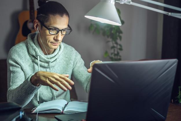 Um jovem estudante do sexo masculino está estudando em uma aula online usando um laptop à noite à luz de uma lâmpada na sala