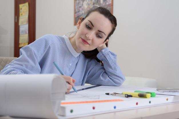 Um jovem estudante prepara o trabalho de arquitetura em uma mesa com um papel de desenho branco e artigos de papelaria