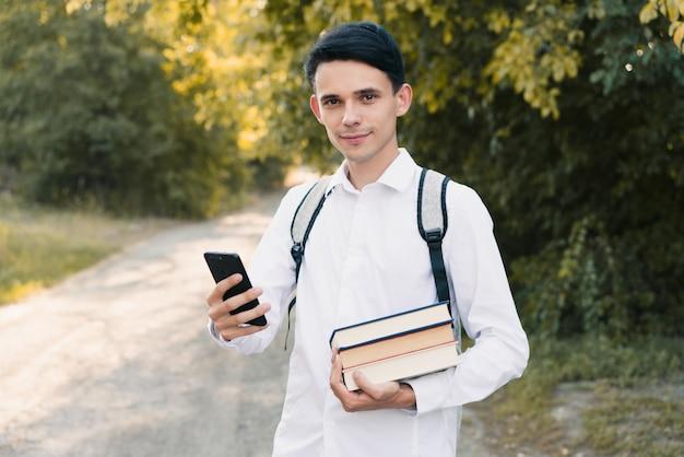 Um jovem europeu em uma camisa branca clássica com uma mochila cinza nas costas segura uma pilha de livros na mão com um telefone e olha diretamente para a câmera, ao ar livre. conceito de educação