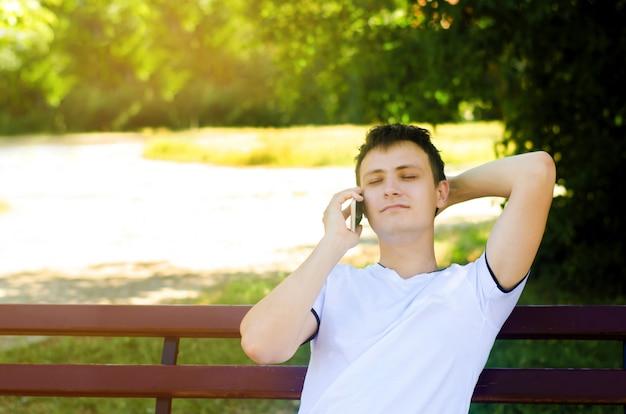 Um jovem europeu está sentado em um banco no parque e falando ao telefone