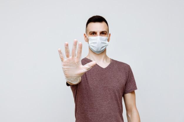 Um jovem europeu usa uma máscara e luvas e mostra um gesto para parar o surto de vírus corona e manter distância