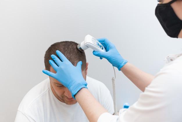 Um jovem examina com um tricoscópio a condição do couro cabeludo e dos folículos capilares.