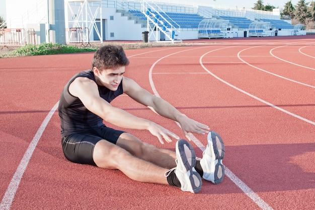 Um jovem faz um atleta de alongamento. no contexto do estádio.