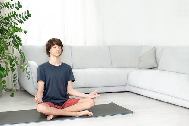 Um jovem faz yoga em casa