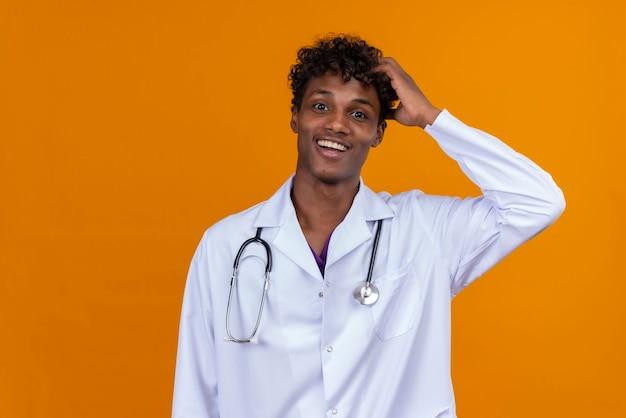 Um jovem feliz, bonito, de pele escura, cabelo encaracolado, jaleco branco e estetoscópio mantendo as mãos na cabeça