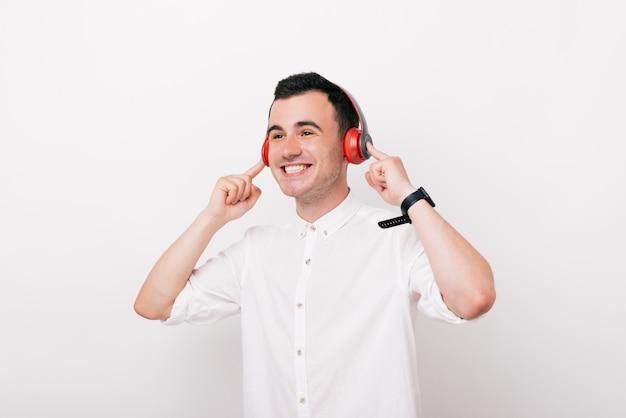 Um jovem feliz está ouvindo a música e sorrindo no estúdio em fundo branco.