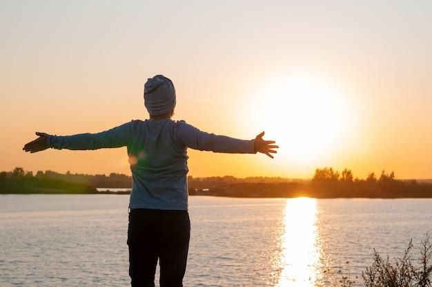Um jovem fica em um lago ao pôr do sol